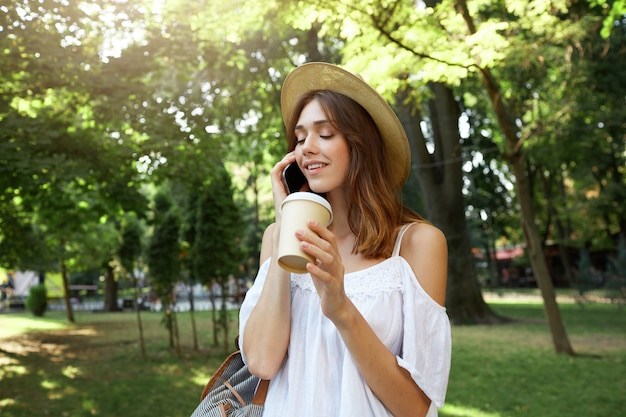 Retrato ao ar livre de uma jovem feliz e fofa com um elegante chapéu de verão e um vestido branco, sentindo-se relaxada, sorrindo e bebendo café para viagem nas ruas da cidade