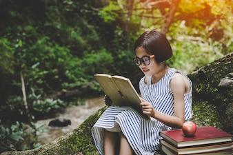 Retrato ao ar livre de uma jovem menina bonitinha lendo um livro