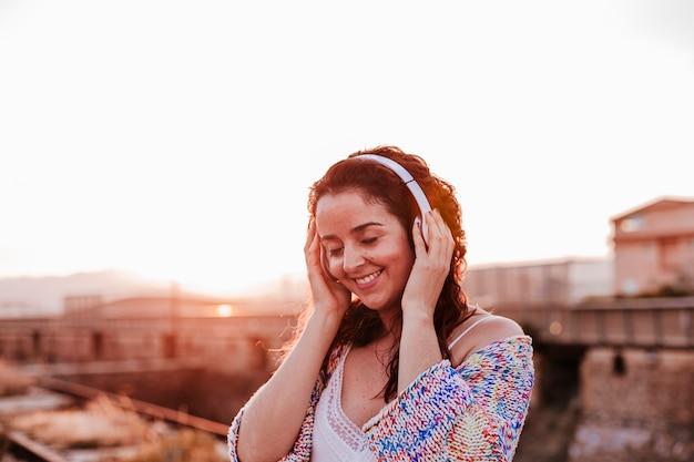 Retrato ao ar livre de uma jovem mulher bonita ao pôr do sol, ouvindo música no fone de ouvido e sorrindo