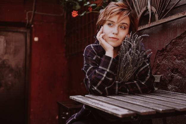 Retrato ao ar livre de uma jovem mulher bonita com cabelo vermelho curto, posando com flor de lavanda. estilo de vida da cidade. menina na cidade velha com paredes vermelhas