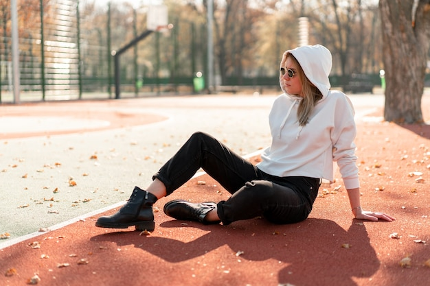 Retrato ao ar livre de uma jovem mulher bonita com long em óculos de sol e um suéter branco com capuz, sentado na pista de sportsground. cultura jovem passatempo de verão
