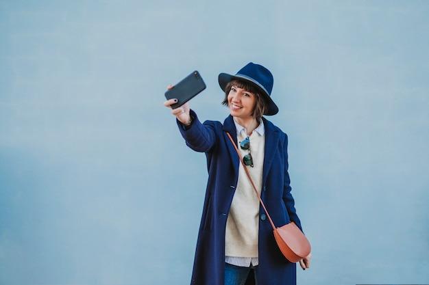 Retrato ao ar livre de uma jovem mulher bonita com roupas elegantes, posando com um chapéu moderno e tomando uma selfie com telefone móvel. estilo de vida