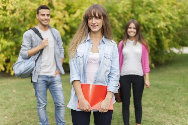 Retrato ao ar livre de uma jovem sorridente na frente de um grupo de estudantes