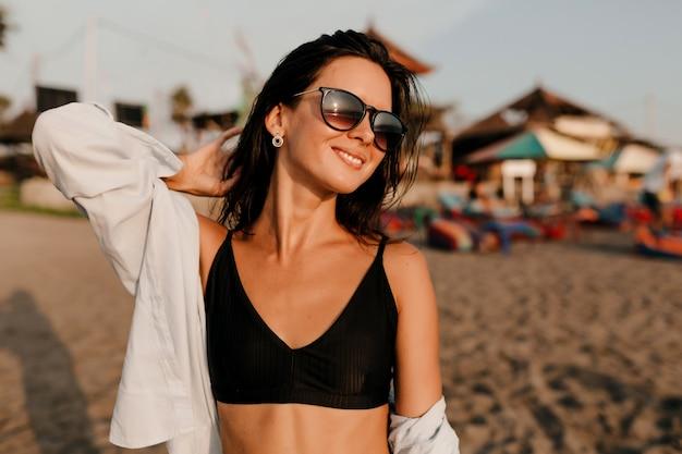 Retrato ao ar livre de uma linda garota encantadora com cabelo escuro, vestindo uma blusa preta e uma camisa posando ao sol na praia de areia