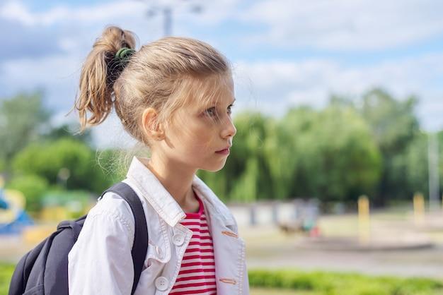 Retrato ao ar livre de uma menina loira no parque
