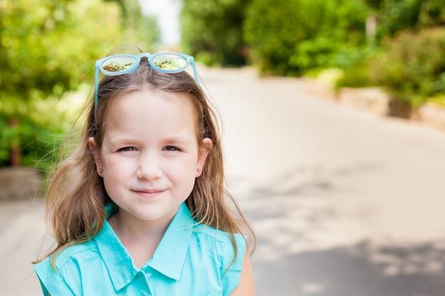 Retrato ao ar livre de uma menina pequena bonito da criança de 5 anos no parque em um dia ensolarado. garoto feliz, garoto sorridente, garota otimista, garota positiva