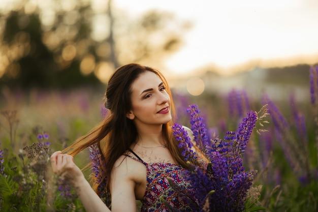 Retrato ao ar livre de uma morena linda jovem idade. garota sexy atraente em um campo com flores