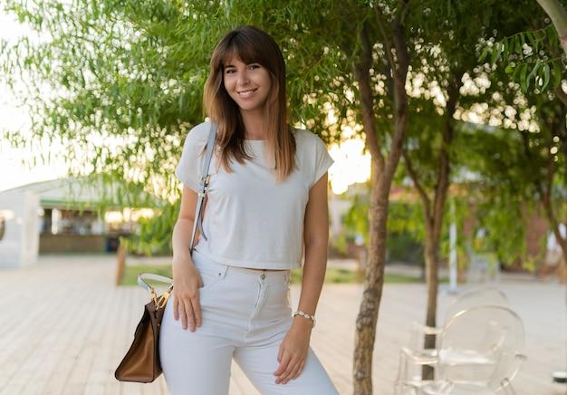 Retrato ao ar livre de uma mulher alegre em jeans e camiseta branca, caminhando no parque.