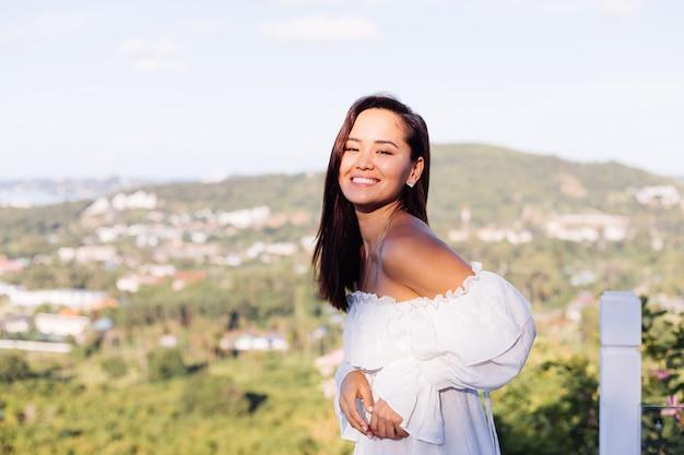 Retrato ao ar livre de uma mulher asiática com vestido branco usando colar e brincos