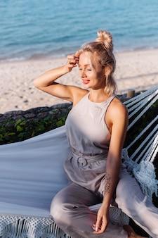 Retrato ao ar livre de uma mulher caucasiana em um macacão clássico com batom vermelho perto da rede nas férias do lado de fora do hotel villa, à beira-mar