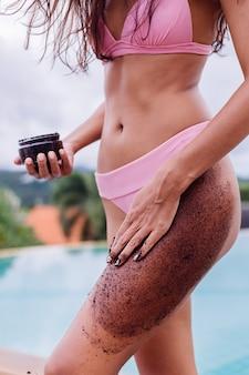 Retrato ao ar livre de uma mulher de biquíni rosa no spa, perto da piscina, segurando um cafezinho