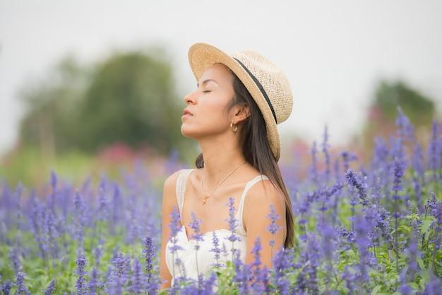 Retrato ao ar livre de uma mulher envelhecida média bonita de ásia. garota atraente em um campo com flores