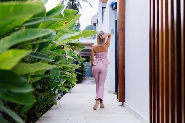 Retrato ao ar livre de uma mulher europeia elegante em um terno rosa