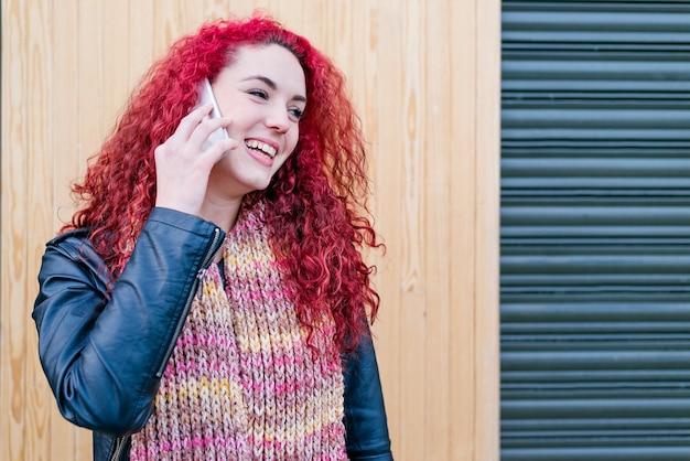 Retrato ao ar livre de uma mulher jovem e atraente com o celular no meio do rua.