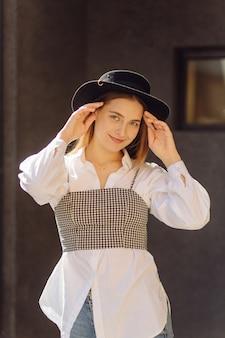Retrato ao ar livre de verão de uma jovem elegante posando em um dia ensolarado na rua