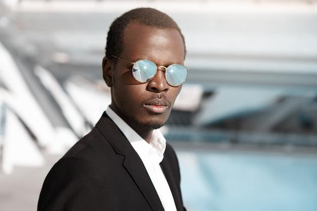 Retrato ao ar livre do atraente empresário americano africano confiante de 30 anos de idade, vestindo terno formal preto e elegantes óculos de sol redondos