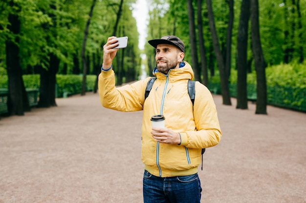 Retrato ao ar livre do bonitão com barba grossa, vestindo jeans e anoraque amarelo segurando a mochila