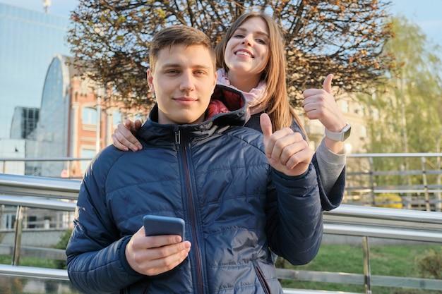 Retrato ao ar livre do casal mostrando sinal de gesto ok
