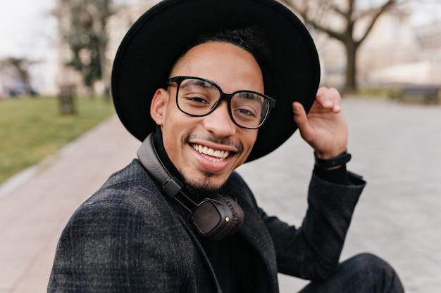 Retrato ao ar livre do close-up de jovem animado com pele morena usa óculos. menino barbudo africano com chapéu, expressando emoções positivas.