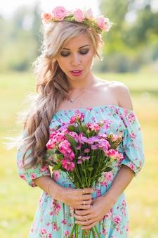 Retrato ao ar livre do close-up de uma linda mulher loira. garota atraente feliz em um campo com buquê de flores.