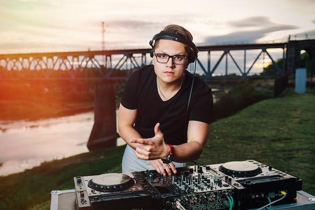 Retrato ao ar livre do criativo jovem dj em copos contra a ponte ao pôr do sol