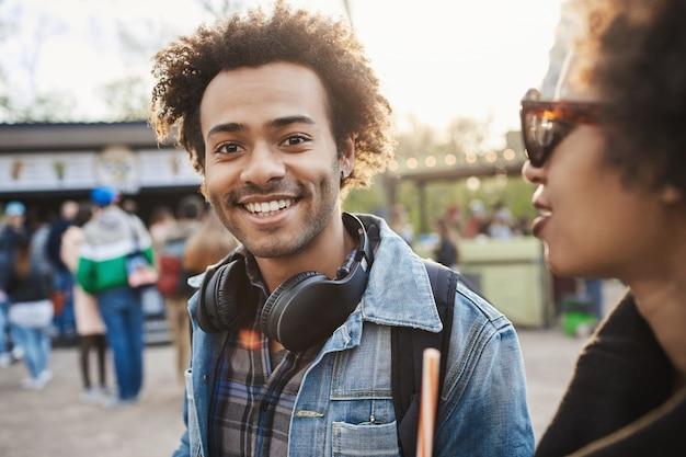 Retrato ao ar livre do encantador homem afro-americano caminhando com um amigo no parque, vestindo roupas jeans e fones de ouvido no pescoço.