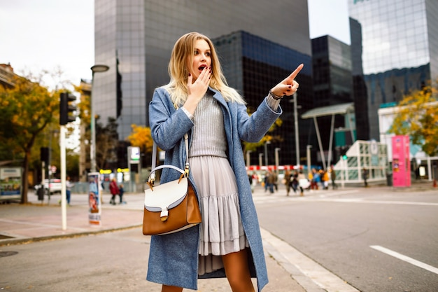 Retrato ao ar livre do estilo de vida da loira muito jovem empresária, caminhando na área de edifícios modernos, vestindo um casaco azul e vestido cinza feminino, surpreendeu as emoções assustadoras, mostrando algo por seu dedo.