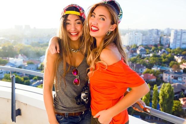 Retrato ao ar livre do estilo de vida das duas melhores irmãs do demônio posando no telhado