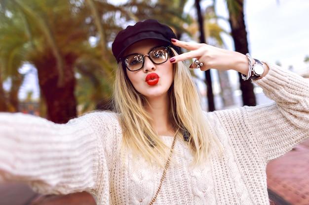Retrato ao ar livre do estilo de vida de feliz elegante jovem fazendo selfie na rua em frente às palmas das mãos, tempo de primavera outono, enviando beijo vestindo uma camisola elegante, óculos e chapéu, clima de viagem.