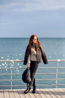 Retrato ao ar livre do estilo de vida de outono de mulher elegante andando sozinho na praia, uma vista incrível sobre o mar, viajar sozinho, moda de rua.