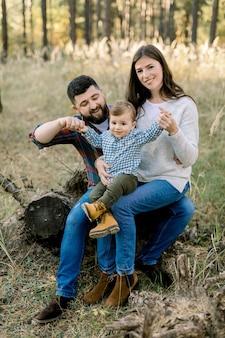 Retrato ao ar livre do estilo de vida de uma família caucasiana feliz, pai, mãe e filho, vestindo roupas casuais elegantes, sentado em um tronco em uma floresta de pinheiros e sorrindo para a câmera