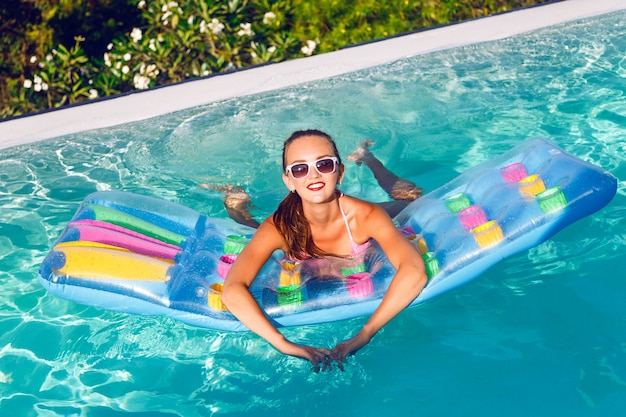 Retrato ao ar livre do estilo de vida de uma jovem deslumbrante se divertindo na piscina infinita com uma vista deslumbrante sobre a ilha tropical, usando biquíni brilhante e óculos escuros, nadando no colchão de ar.