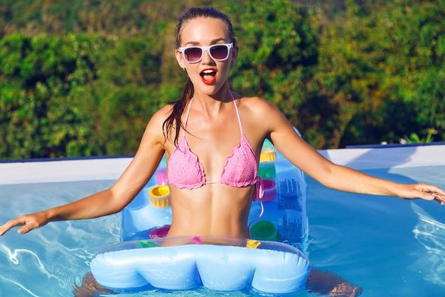 Retrato ao ar livre do estilo de vida de uma mulher muito sexy de férias, usando biquíni brilhante e óculos escuros, relaxando e se divertindo na festa na piscina