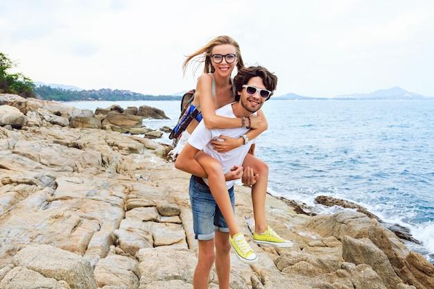 Retrato ao ar livre do estilo de vida do jovem lindo casal apaixonado, posando e se divertindo na praia de pedras, em tons suaves.