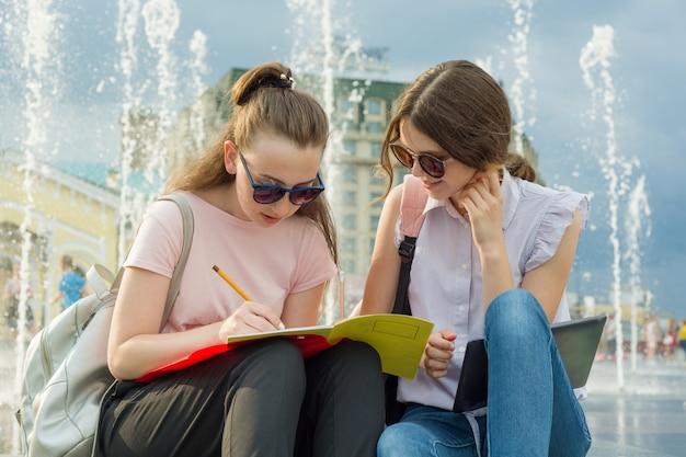 Retrato ao ar livre do estudante de meninas com mochilas