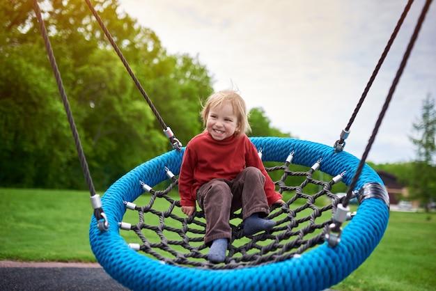 Retrato ao ar livre do garoto bonito rindo criança balançando em um balanço no parque infantil