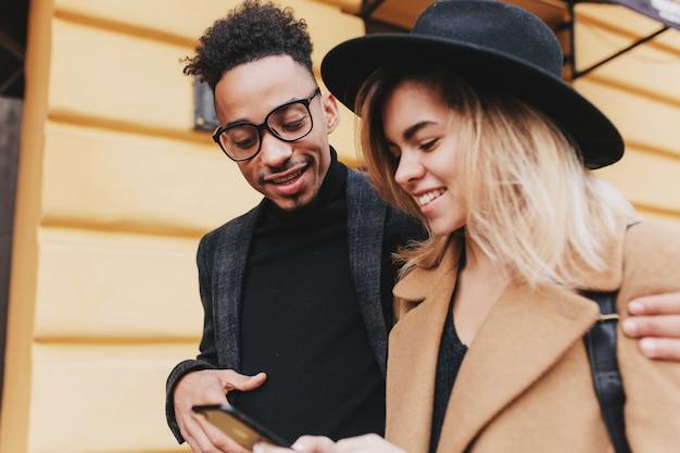 Retrato ao ar livre do homem africano interessado, andando pela rua com uma mulher loira magnífica. garota europeia sorridente se divertindo com o negro animado.