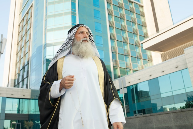 Retrato ao ar livre do homem árabe sênior sério.