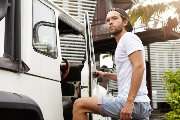 Retrato ao ar livre do homem barbudo elegante em shorts jeans, entrar em seu veículo utilitário esportivo branco, segurando a mão no punho