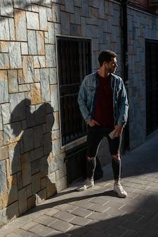 Retrato ao ar livre do homem novo moderno com o telefone esperto na rua.
