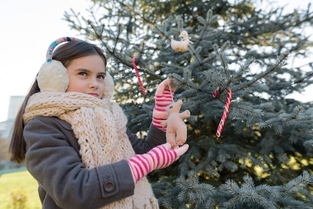 Retrato ao ar livre do inverno da menina criança perto da árvore de natal.