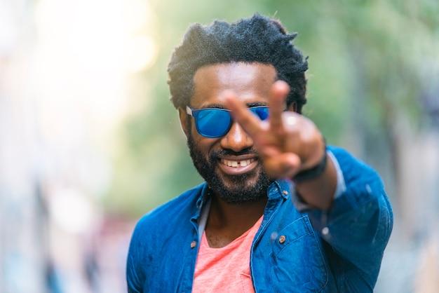 Retrato ao ar livre do jovem africano bonito, fazendo o sinal de vitória.
