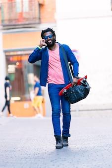 Retrato ao ar livre do jovem africano bonito usando o celular na rua.