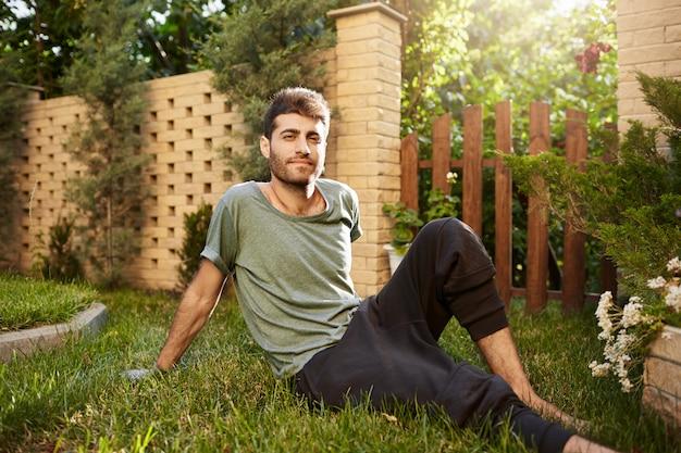 Retrato ao ar livre do jovem atraente barbudo caucasiano jardineiro masculino sorrindo, sentado na grama no jardim.