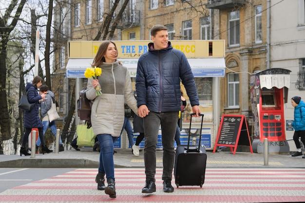 Retrato ao ar livre do jovem casal andando com mala na cidade