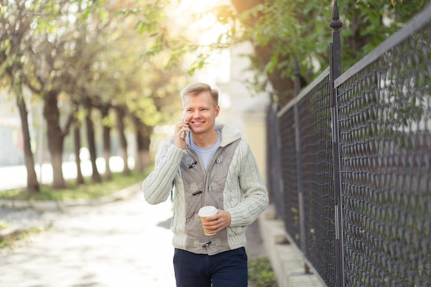 Retrato ao ar livre do jovem moderno falando com o celular na rua da cidade