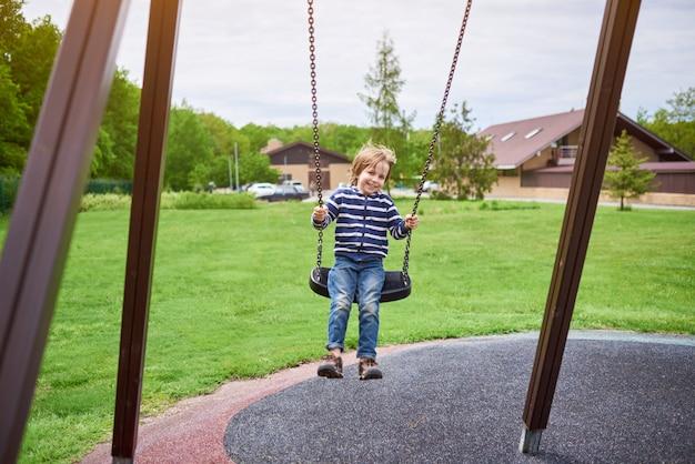 Retrato ao ar livre do menino risonho pré-escolar fofo balançando em um balanço no parque infantil