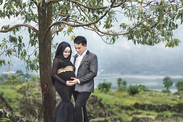 Retrato ao ar livre do momento romântico de um casal grávida debaixo da árvore