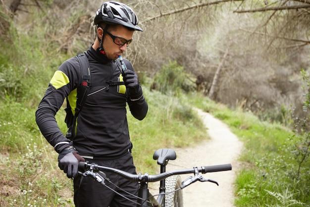 Retrato ao ar livre do piloto profissional bonito em roupas de ciclismo, segurando o guidão da bicicleta motorizada preta, água potável fora do tubo de plástico durante uma pequena pausa enquanto andava na floresta