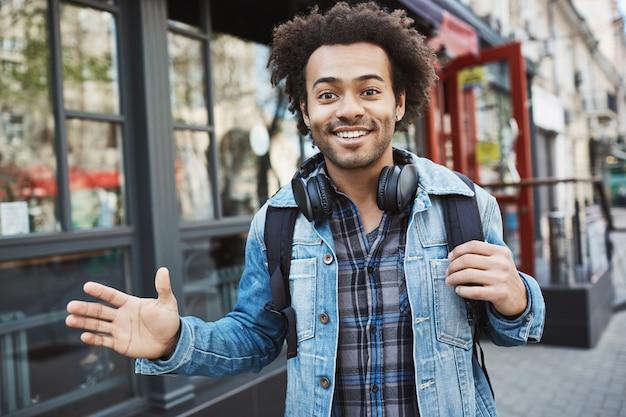 Retrato ao ar livre do positivo afro-americano com penteado afro, acenando e sorrindo enquanto caminhava na rua, usando roupa da moda e fones de ouvido no pescoço.